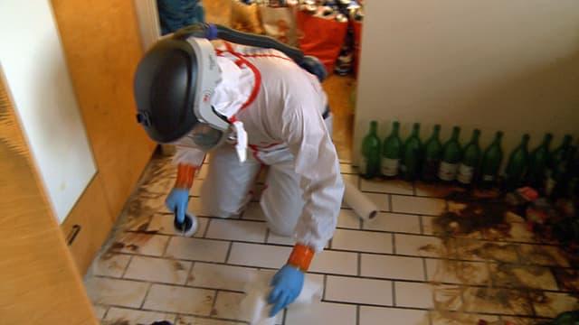 Ein Mann mit Atemmaske und Schutzanzug putzt den Boden in einer Wohnung.