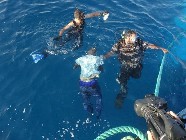 Ein Ertrunkener wird von Tauchern aus dem Meer geholt.