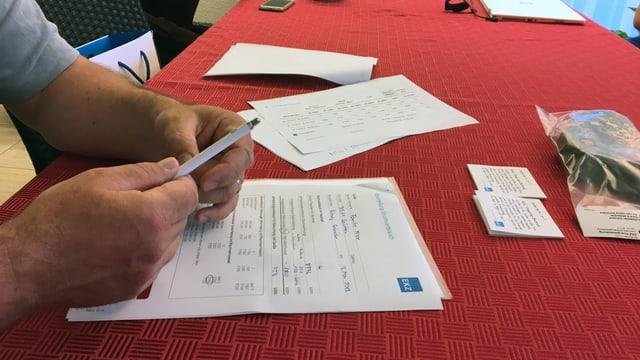 Ein Stromrechnung liegt auf einem roten Tischtuch, eine Hand mit einem Kugelschreiber