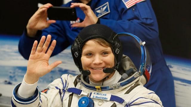 Anne McClain in Astronautenuniform, winkt ins Bild.