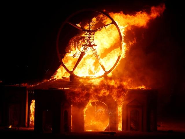 Die Holzfigur des Burning Man steht in Flammen.