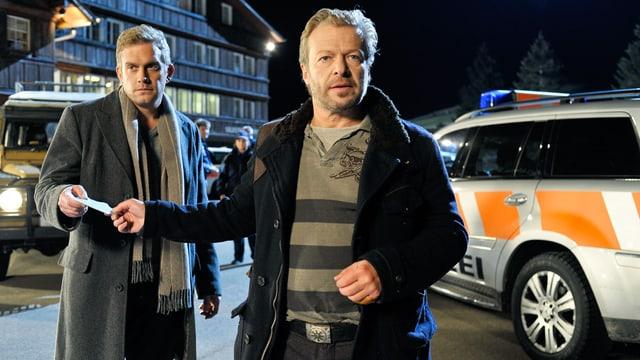 Zwei Männer stehen vor Polizeiwagen. Der vordere reicht dem hinteren ein Stück Papier.
