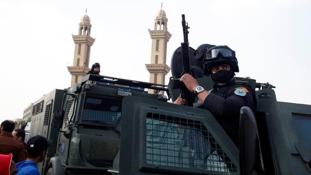 Gepanzerter Wagen mit ägyptischen Sicherheitskräften vor einer Moschee mit zwei Minaretten.