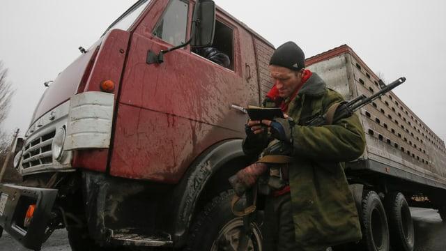 Ein prorussishcer Separatist blättert in einem Notizbuch, er trägt ein Gewehr und steht vor einem Lastwagen.