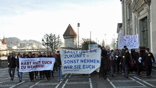 Jugendliche mit Transparenten an einer Demo gegen Abbaupläne in der Bildung.