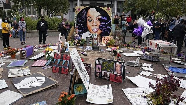 Plakate einer jungen Frau und Kerzen zieren einen Vorplatz