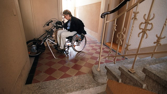Eine Rollstuhlfahrerin in einem Treppenhaus eines Wohnhauses.