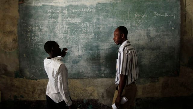 Ein Lehrer und ein Schüler vor einer Wandtafel