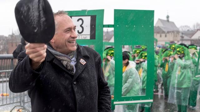 Politiker an der Fasnacht mit winkt mit dem Hut.