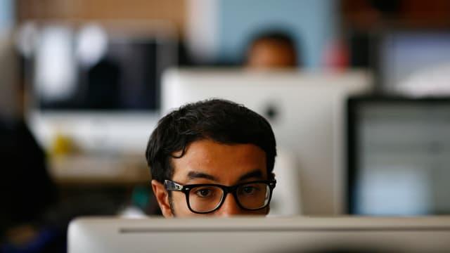 Ein Freelancer eines kanadischen Startups in Kathmandu, konzentriert vor seinem Bildschirm sitzend.