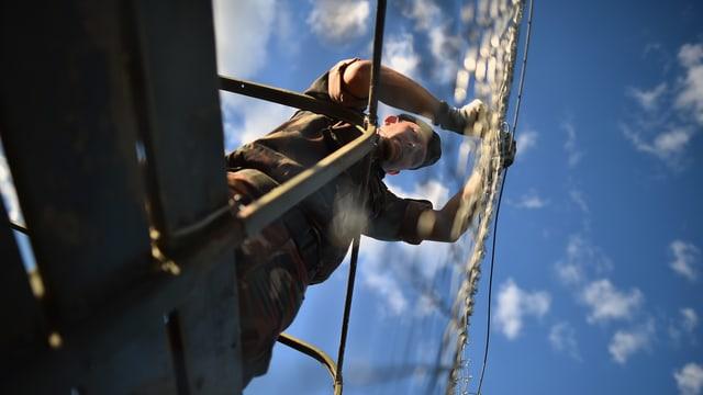 Ein uniformierter Mann arbeitet an einem Gitterzaun, fotografiert von unten gegen den blauen Himmel.