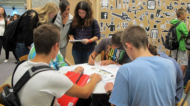 Jugendliche sitzen und stehen um einen Tisch an der Ostschweizer Bildungsausstellung.
