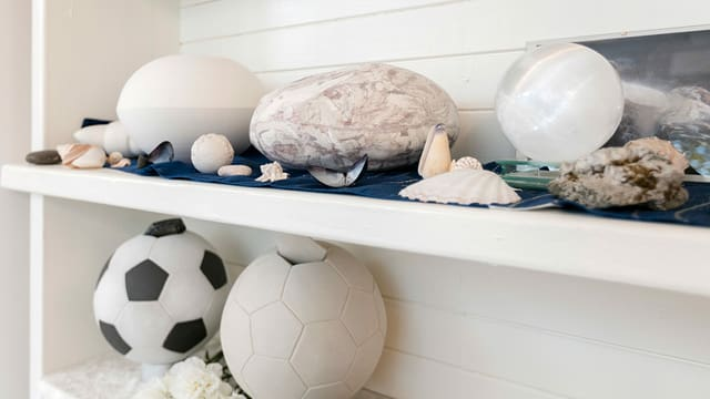 Ungewöhnliche Urnen in einem weissen Regal.