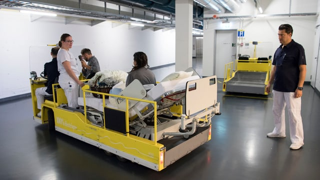 Krankenbett und Pflegepersonal bei Transport.