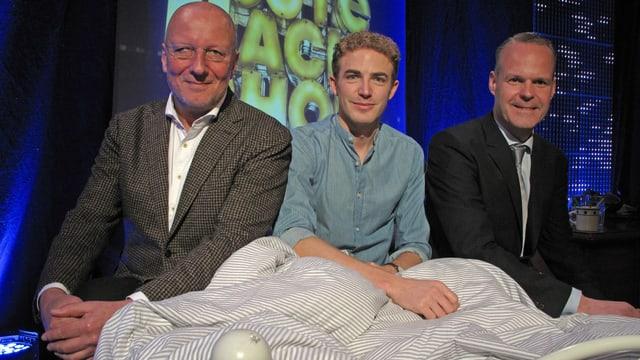Drei Männer sitzen auf einem Bett.
