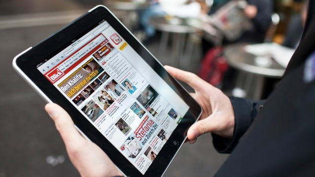 Eine Person hält ein Tablet in den Händen und liest den Blick online.