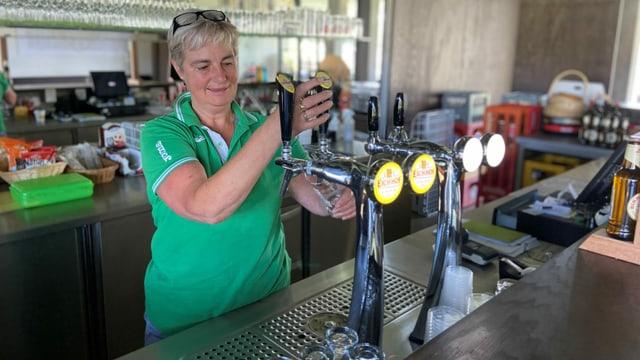 Eine Frau zapft am Tresen ein Bier.