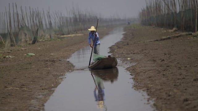 Ein Fischer rudert einen Fluss entlang, der zu einem schmalen Strom ausgetrocknet ist.