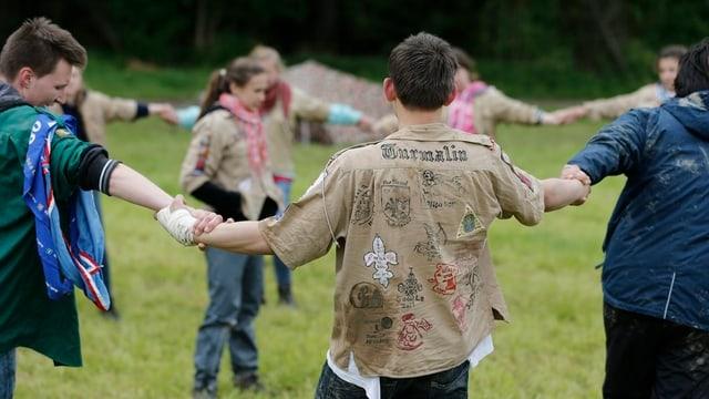 Jugendliche Pfadis halten sich an den Händen und bilden einen Kreis.