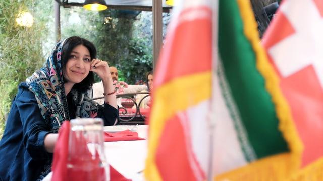 Eine Frau sitzt im Restaurant, im Vordergrund: die Iran und die Schweizer Flagge