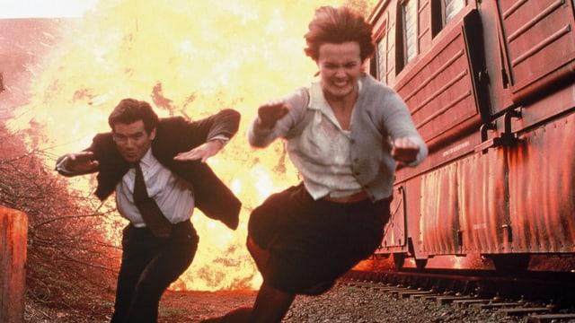 Ein Mann und eine Frau rennen aus einem explodierenden Hochsicherheitszug.