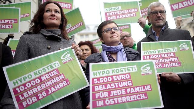 Parteimitglieder mit grünen Plakaten gegen die Hypo-Pleite.