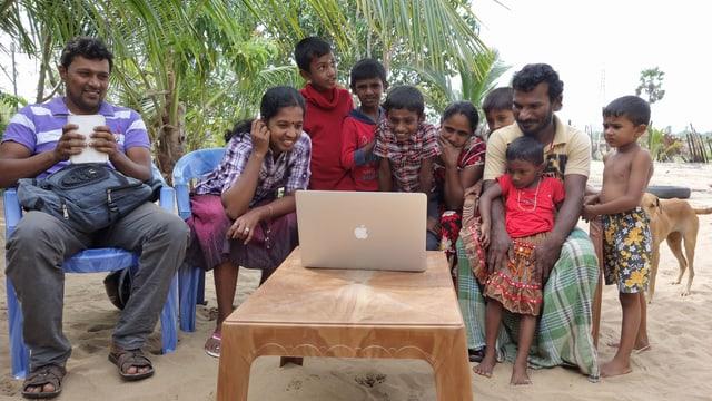 Menschen schauen Film auf Computer am Strand