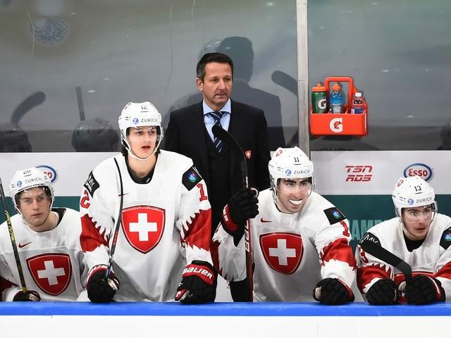Trainer Marco Bayer und 4 Spieler auf verfolgen das Spielgeschehen.