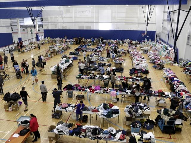 Turnhalle voller Tische mit Kleidern.