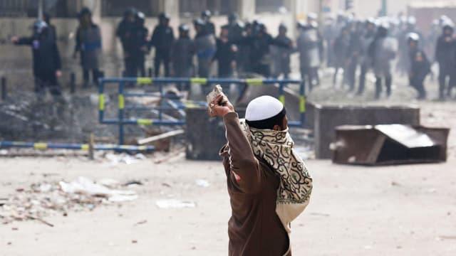 Ein Mann wirft Steine auf Polizisten. Die Szene spielt sich in Kairo ab.