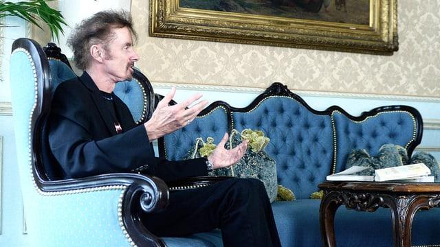 Der Autor T.C. Boyle mit dunklen Kleidern sitzt auf einem Fauteuil, die Hände in der Luft.