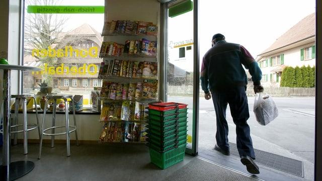 Eine Frau in einem Dorfladen, der auch Post ist