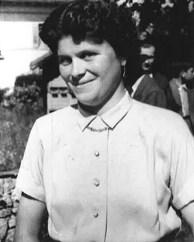 Schwarz-Weiss Fotografie mit der jungen dunkelhaarigen Frau, die eine helle Bluse trägt.