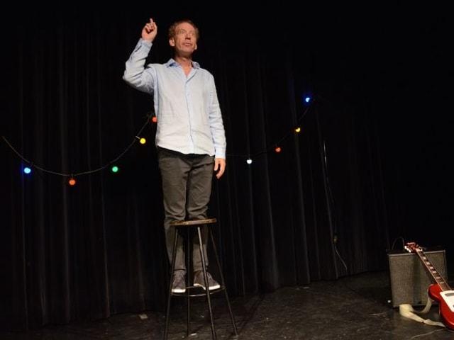 Ein Mann auf einer Bühne steht auf einem Barhocker und streckt die rechte Hand in die Luft.