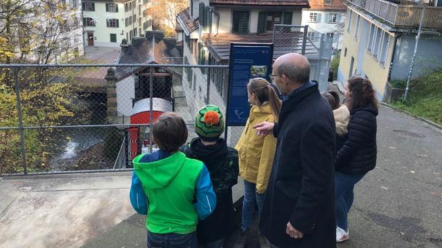 Kinder und ein Mann schauen auf die Mühleggbahn.