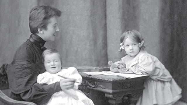 Frau sitzt an Tisch mit zwei Kleinkindern.