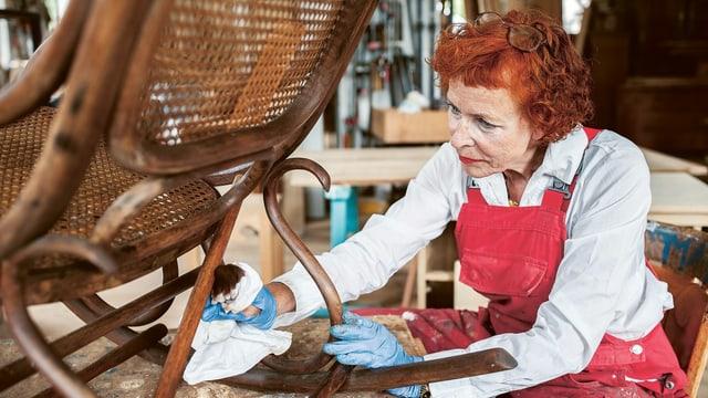 Eine Frau putzt einen Stuhl.