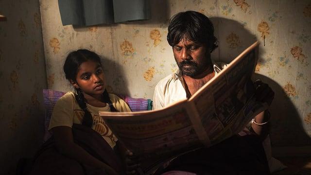 Ein junges Mädchen und ein Mann sitzen nebeneinander auf dem Boden mit einer Decke über den Beinen. Der Mann hält eine Zeitung, in der beide lesen.