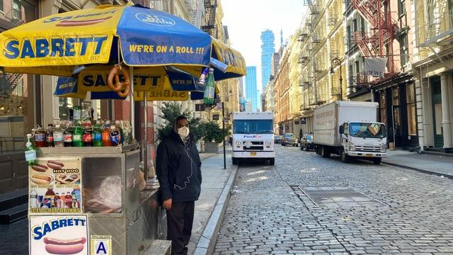 Ein Mann steht am Strassenrand neben einem Essensstand für Hot Dogs.