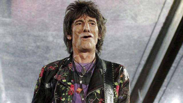 Ron Wood steht in Lederjacke auf der Bühne während eines Konzerts.
