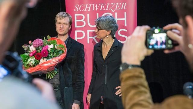 Ein Mann mit Blumenstrauss in der Hand und eine Frau werden aus Distanz fotografiert.