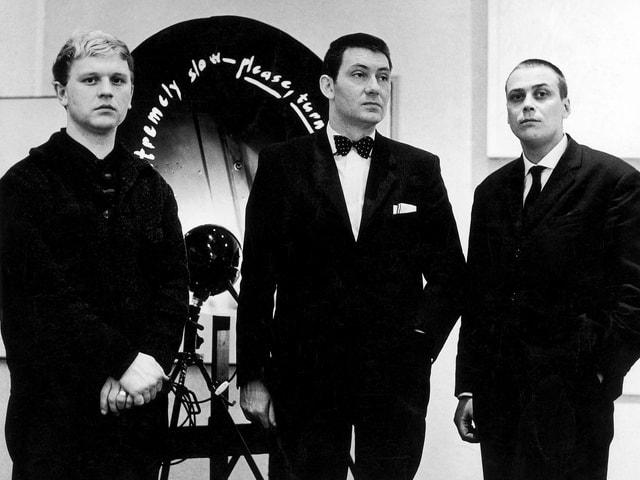 Drei Männer in schwarzen Anzügen, nebeneinander stehend (s/w).