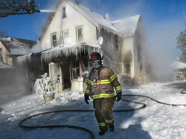 Feuerwehrmann vor vereistem Haus