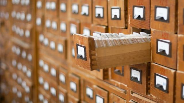 Alter Zettelkasten mit vielen Schubladen, eine ist herausgezogen.