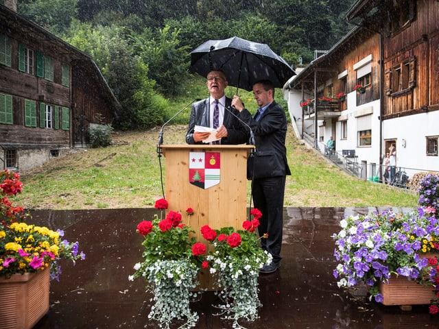 Bild vom Regierungspräsidenten, wie er mit einem Schirm vom Regen beschützt wird