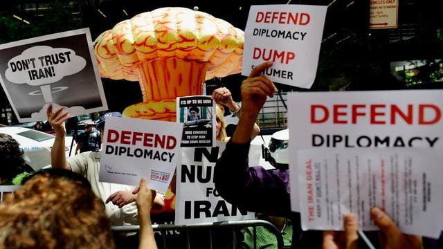 Protestplakate gegen und für das Atomabkommen