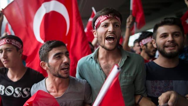 Junge Männer rufen an einer Demonstration Slogans gegen die PKK