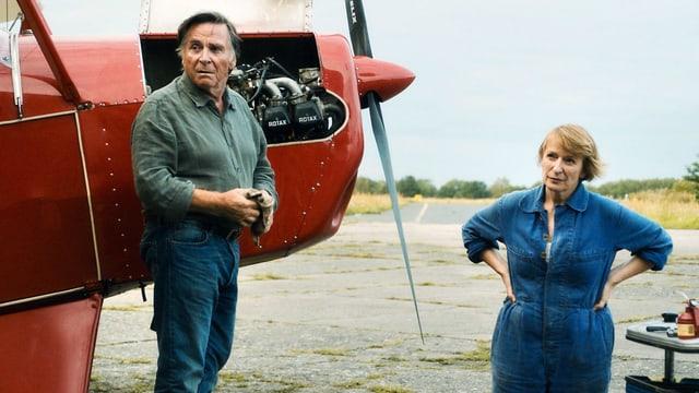 Ein Mann und eine Frau stehen neben einem Flugzeug.