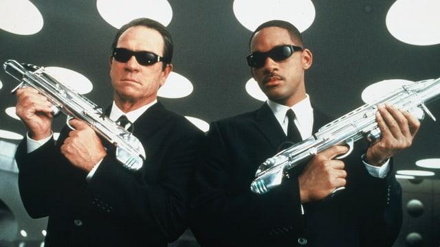 Zwei Männer mit futuristischen Schusswaffen.