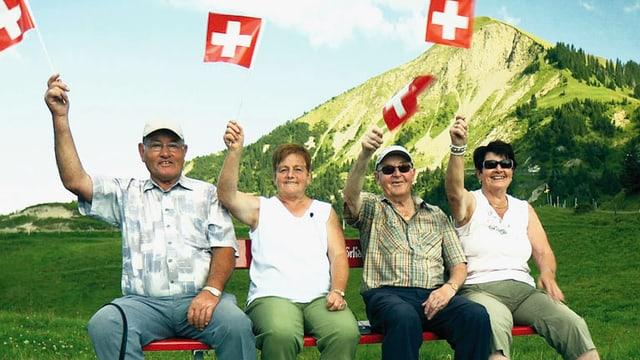Zwei Männer und zwei Frauen sitzen auf einer Parkbank. Sie schwingen alle eine Schweizer Fahne in der Luft. Im Hintergrund ist ein Berg zu sehen.